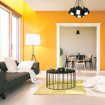 Color consultation for Modern room with gold wall paint, white trim, light floor and charcoal sofa from paint color consultation.