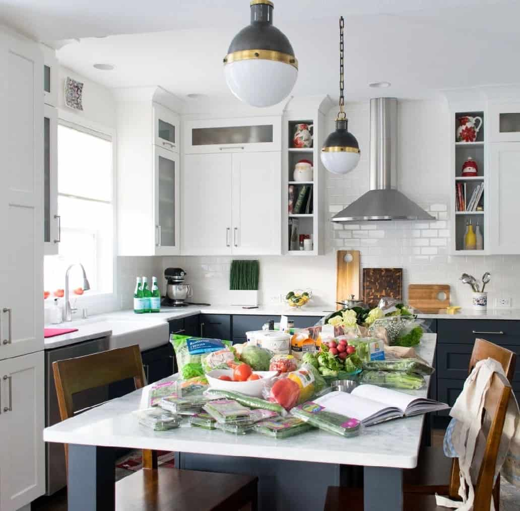 classic kitchen with tuxedo cabinets, subway backsplash, marble counters and groceries on island