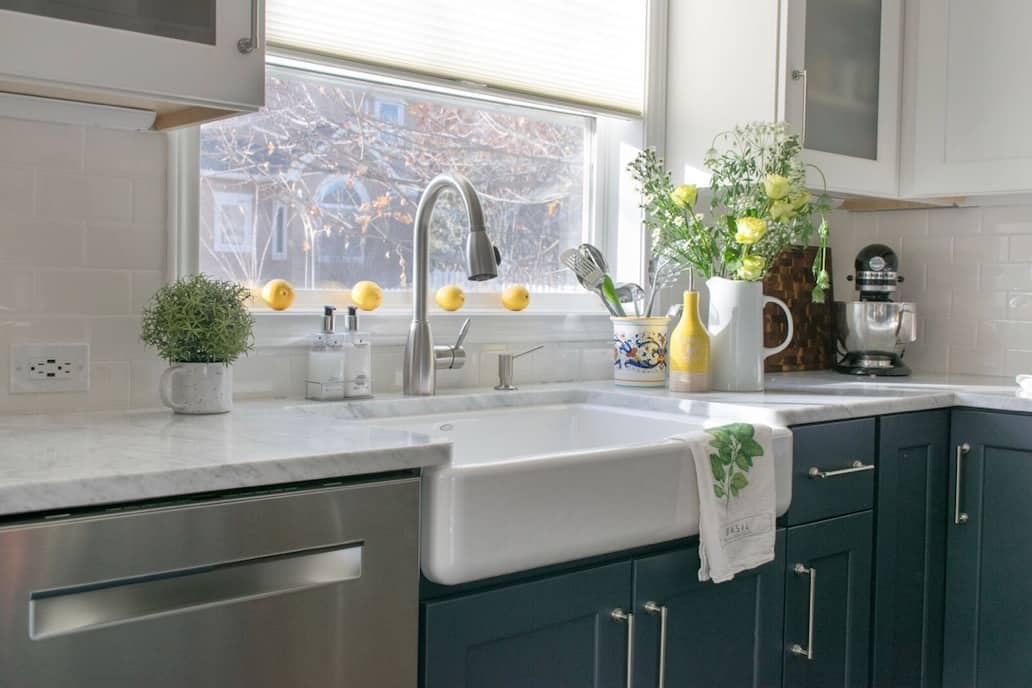 Farmhouse sink in classic kitchen remodel with carrara marble kitchen counters