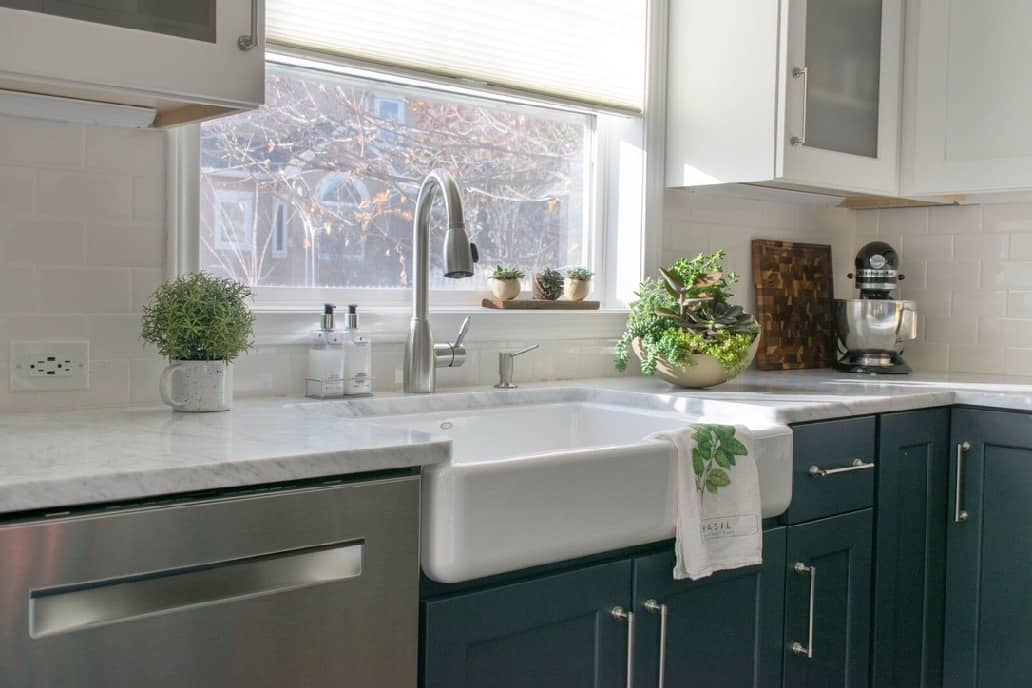 3 Ways to Style your Farmhouse Sink. Farmhouse sink styled with green accents in a kitchen remodel
