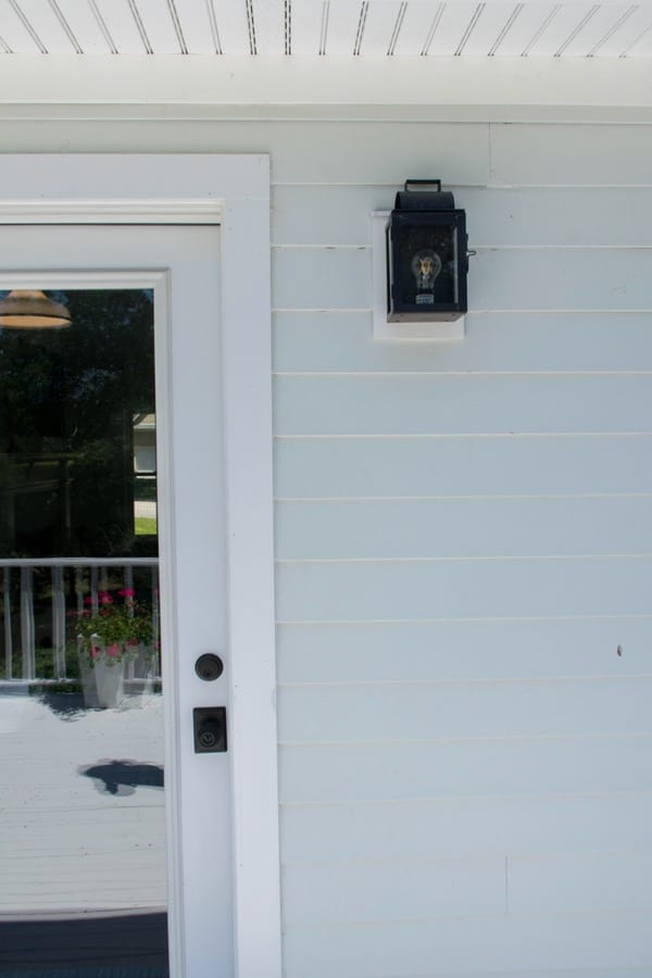 Coastal cottage exterior white door with black hardware and lighting and james hardie arctic white siding