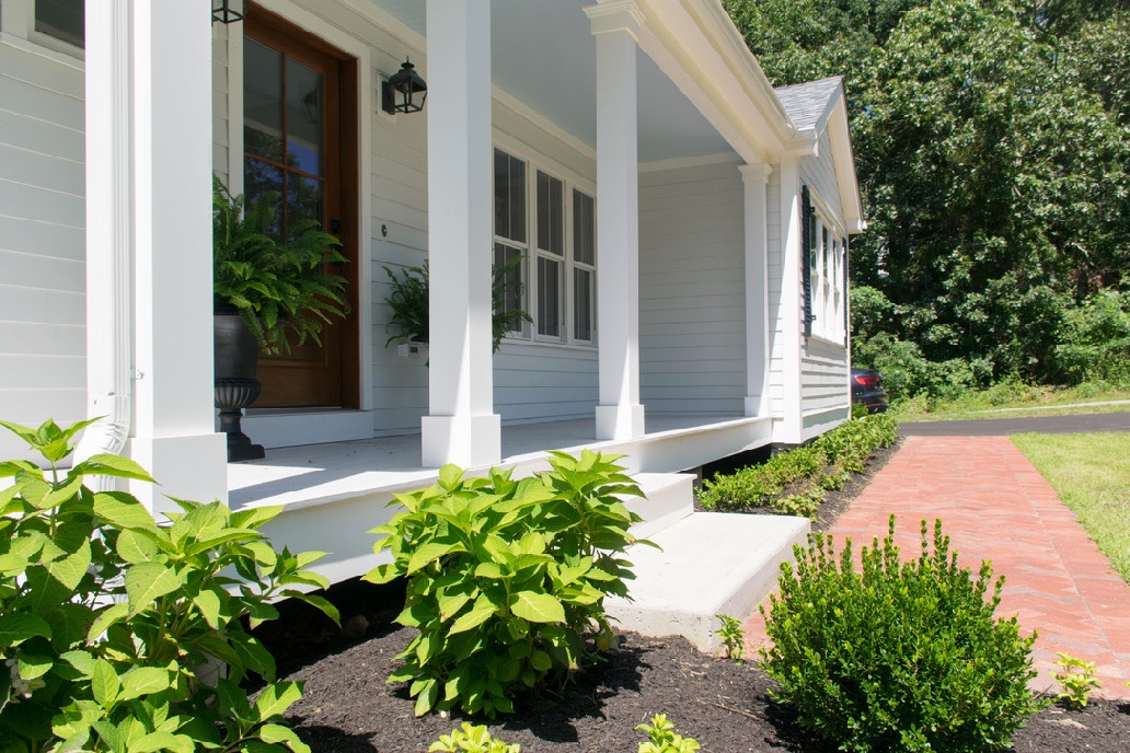 White coastal cottage exterior with front porch blue ceiling and SW Zircon deck floor with wood door and black hardware.