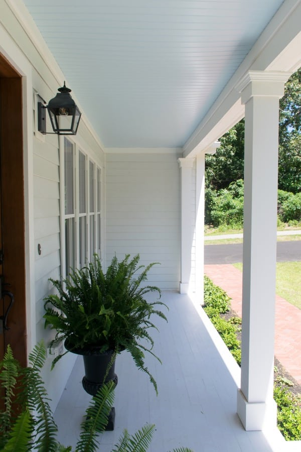 Coastal cottage exterior and front porch with haint blue ceilings and light gray deck.