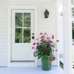 Coastal cottage back porch with blue ceiling and light gray deck with a white door and pink geraniums.