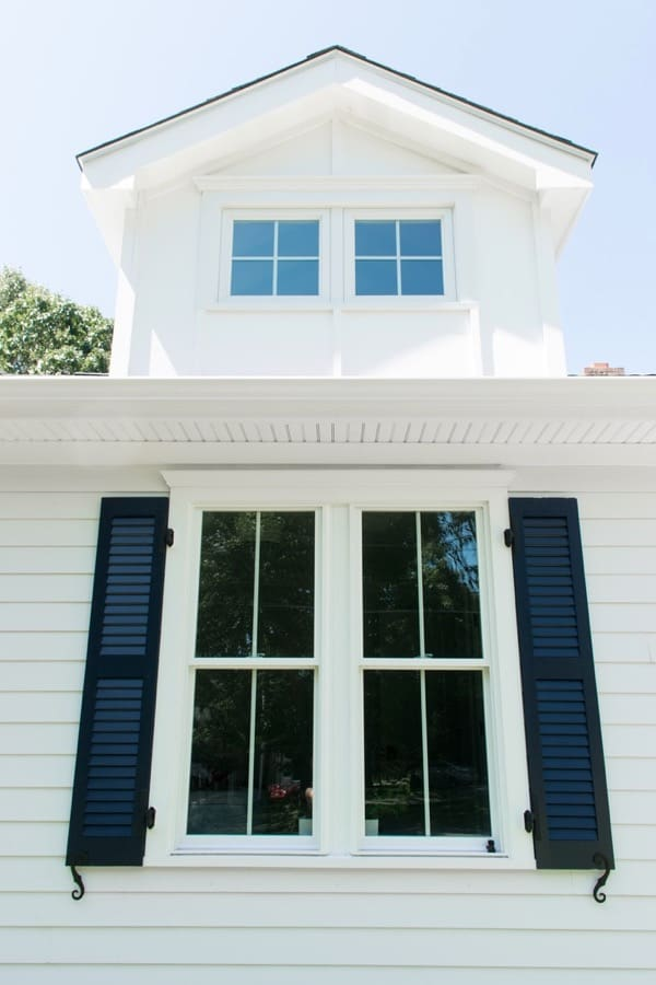 White coastal cottage with gable and dark blue shutters
