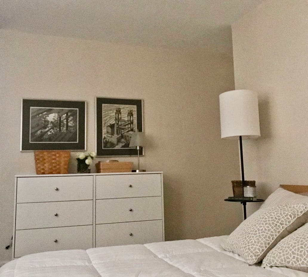 White dresser and bed with Escher prints and green beige pillows.