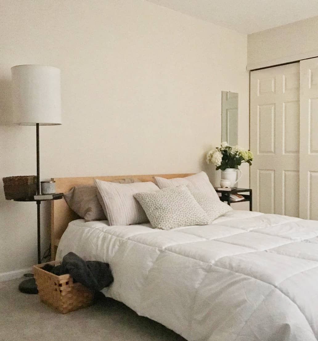 White bed with beige pillows and wood Ikea Malm bedframe