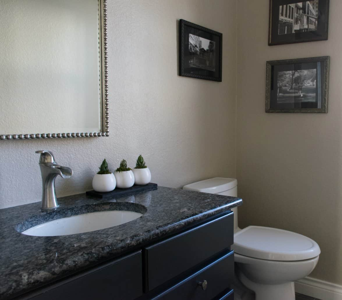Powder room with granite, black and white photos and square mirror.