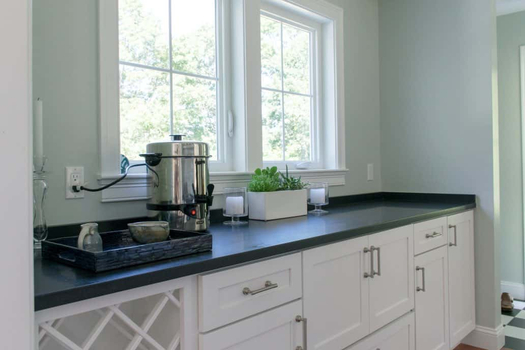 Butler's pantry with black counters, white cabinets, SW Sea Salt walls and coffee service.