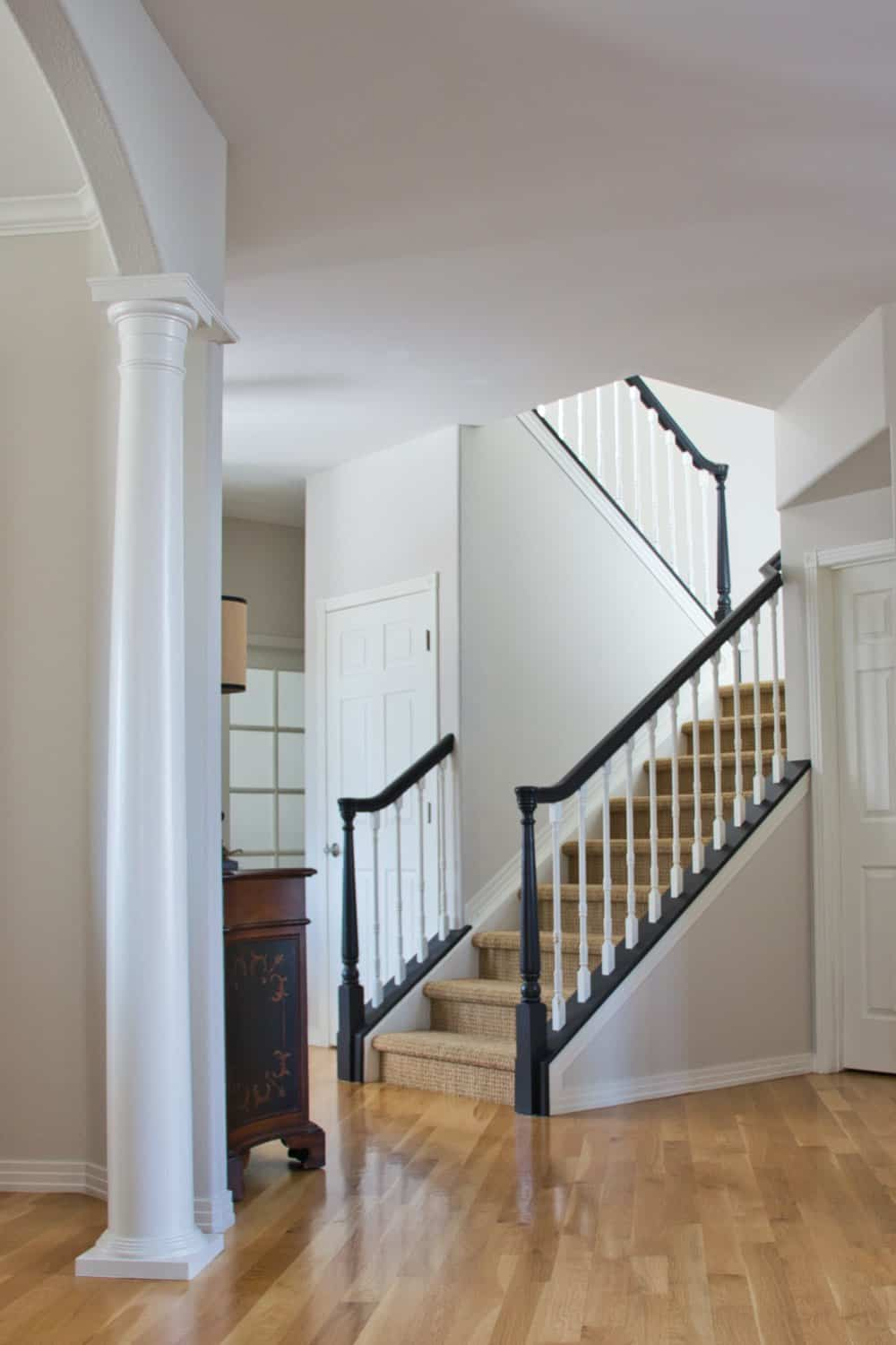 Traditional stairway painted with Classic Gray walls, Simply White trim and Tricorn Black handrails.