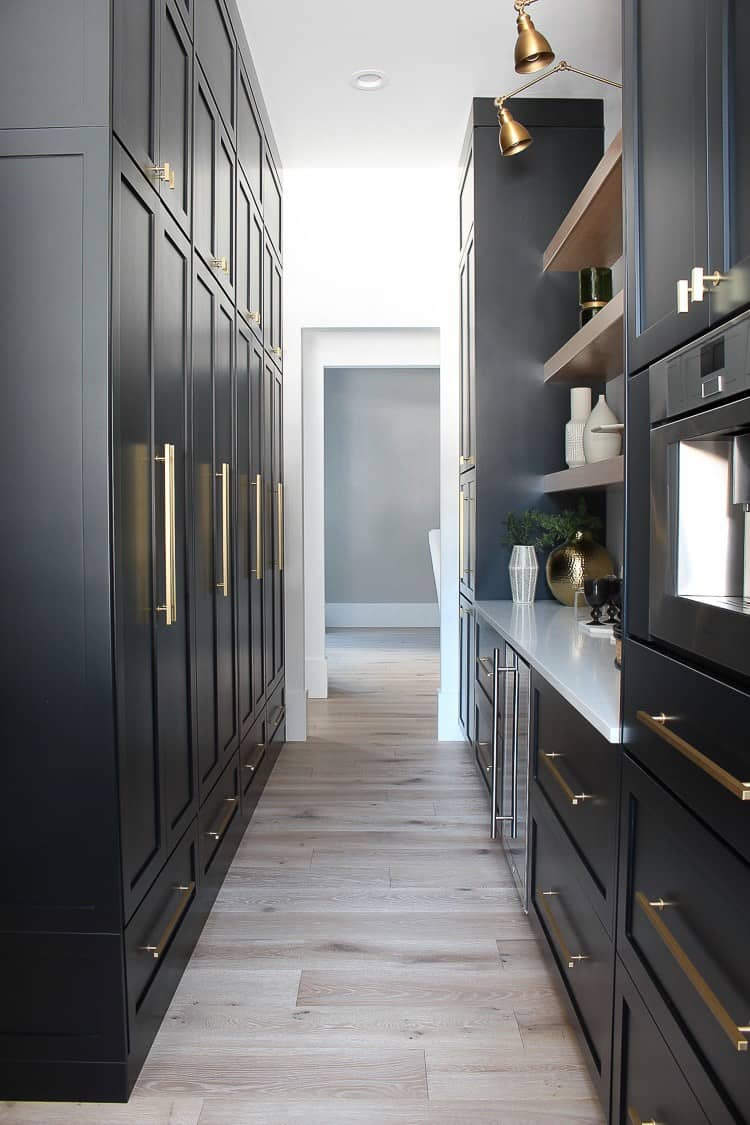 Butler's pantry with black cabinets, gold hardware and lights and white counters.