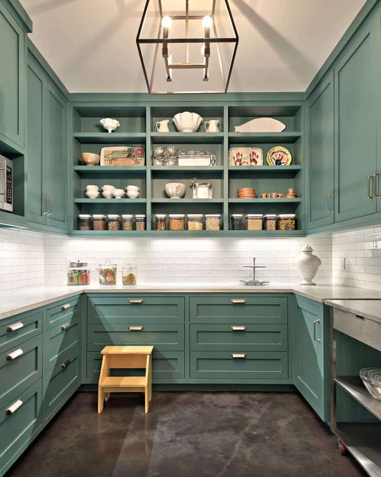 Butler's pantry with green cabinets, white counters and a linear chandelier.