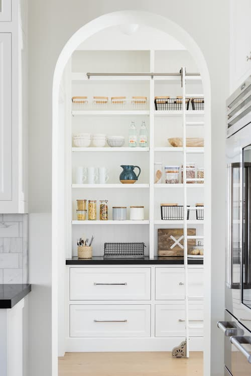 White butler's pantry with black counters, open shelves, ladder and arched doorway