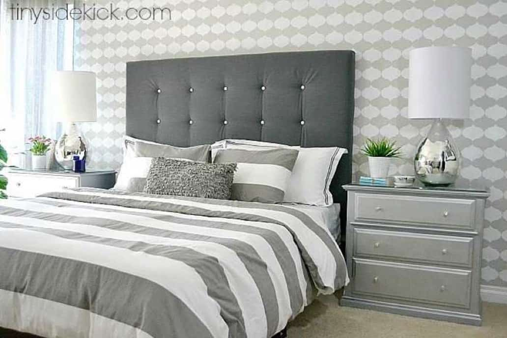 Bedroom with gray checked wallpaper and a gray upholstered headboard.
