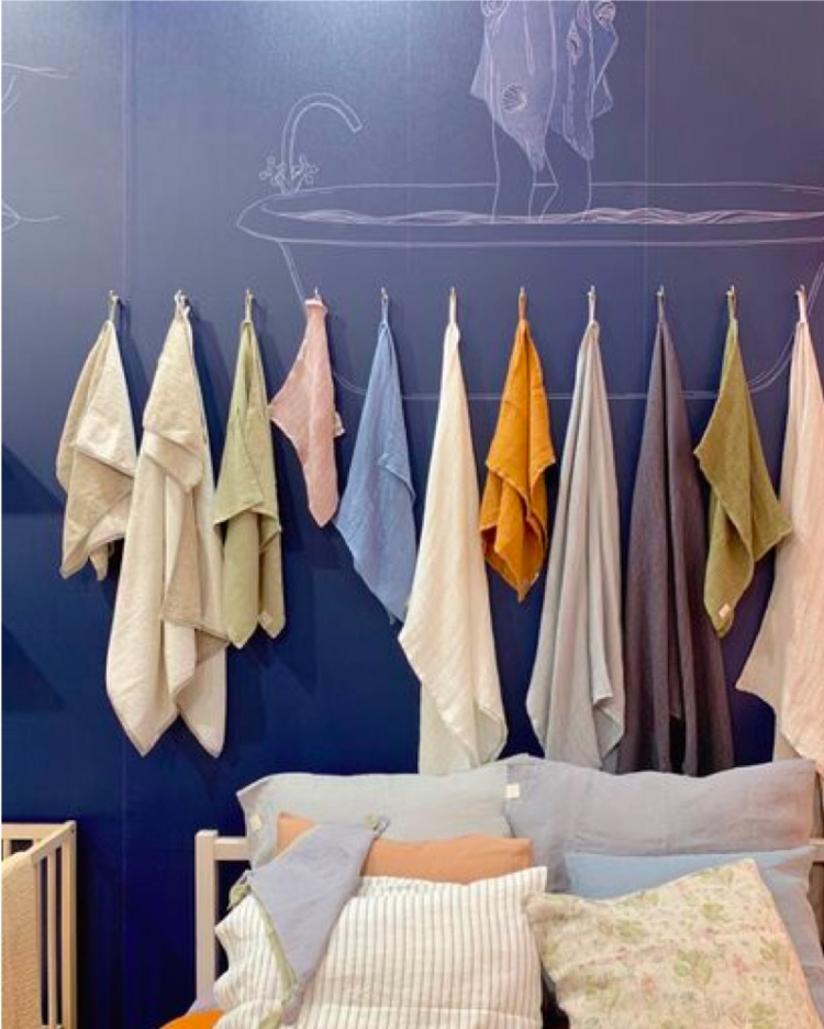 Bed with colorful linens and hanging colorful towels from Maison d'Objet predict paint color trends