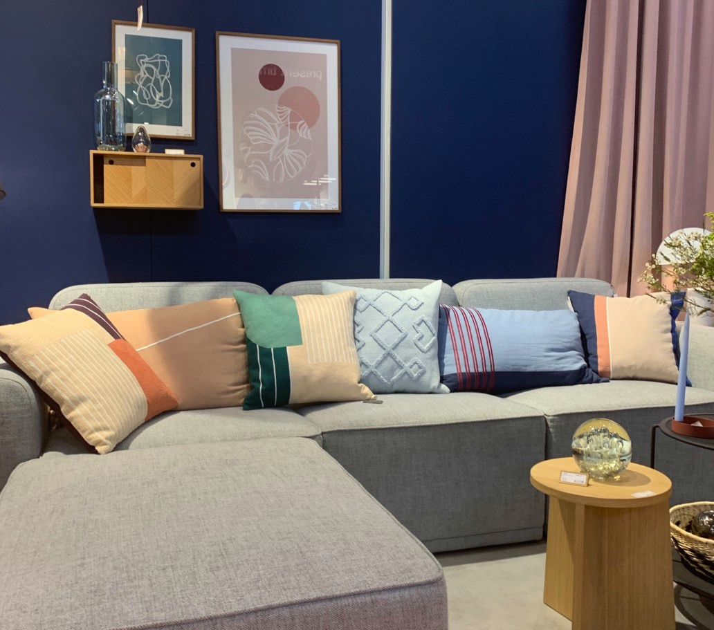 Beige couch with colorful pillows and dark blue walls predict paint color trends
