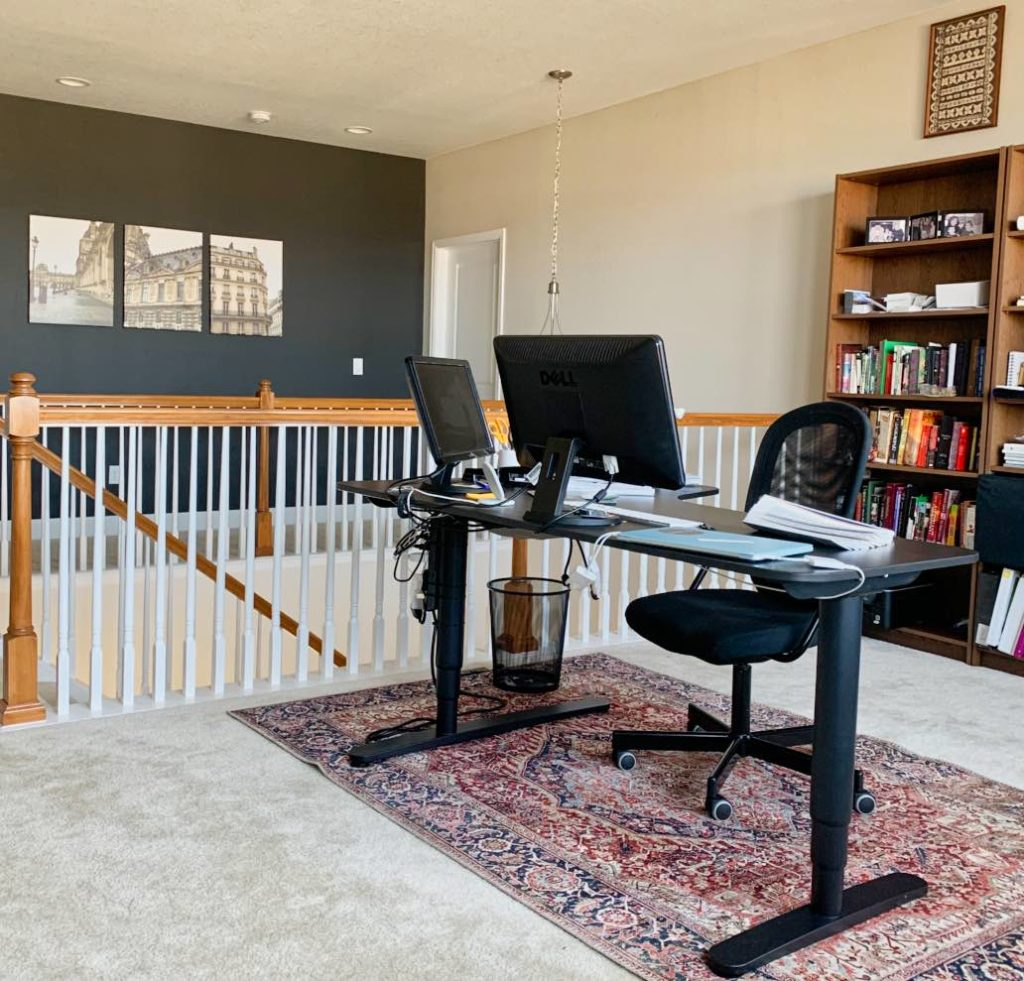 Home office in loft area with SW Iron Ore accent wall and SW Agreeable Gray Walls