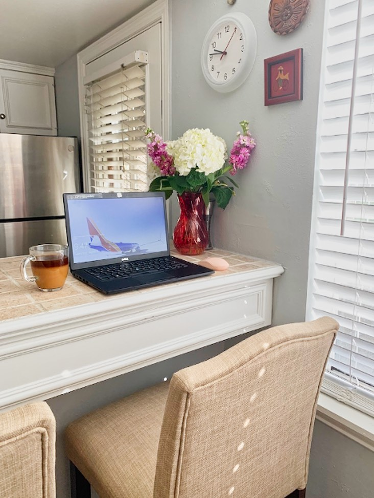 Home office in kitchen counter with laptop and Benjamin Moore Shoreline walls.