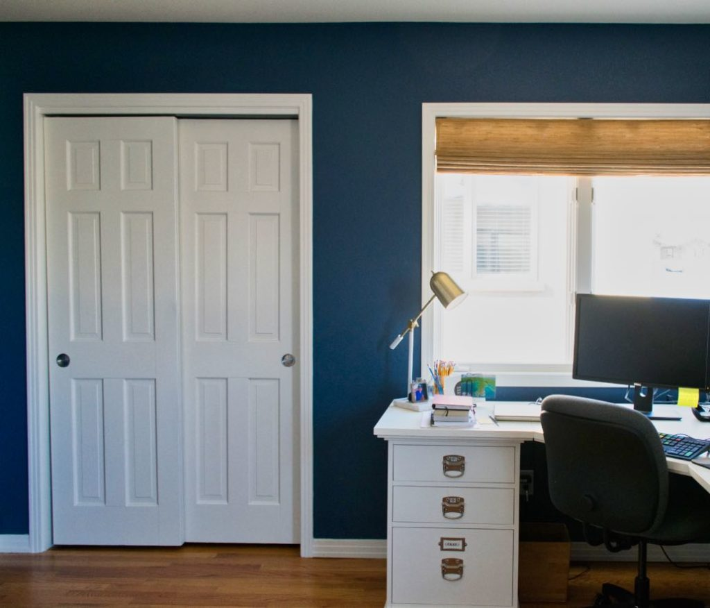 Home office with white desk, bamboo shades and BM Kensington Blue Walls