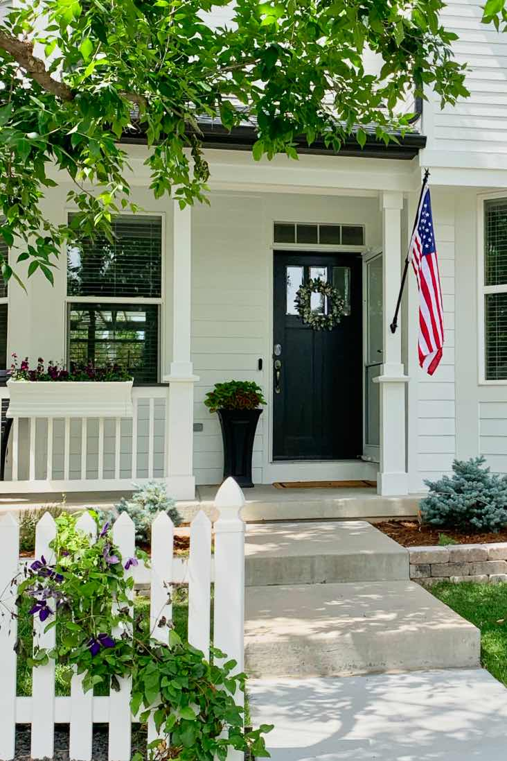 white house with farmhouse white paint color, black front door, white picket fence and American flag