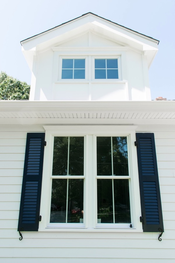 White farmhouse window with blue shutters