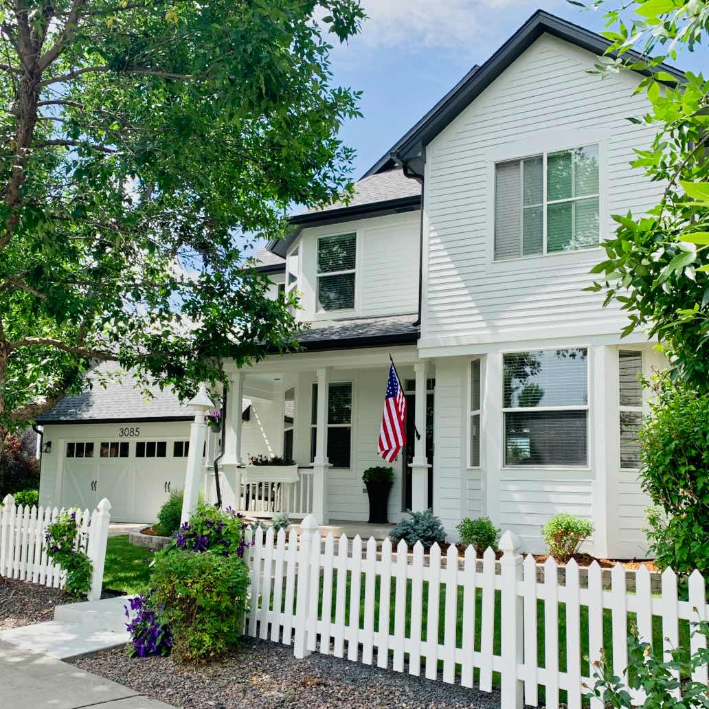 house with farmhouse white paint color, white picket fence and American flag