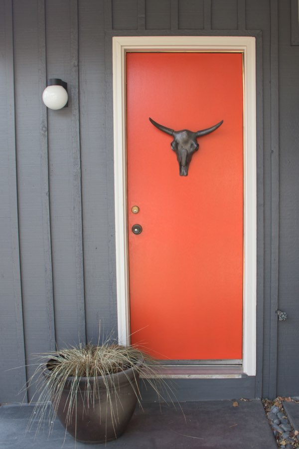 Orange front door with white trim and blue siding