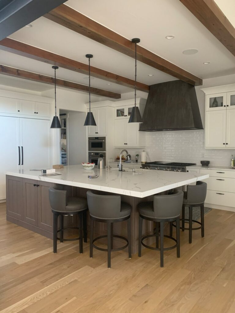 Kitchen with white cabinets and rift oak island with Simply White walls