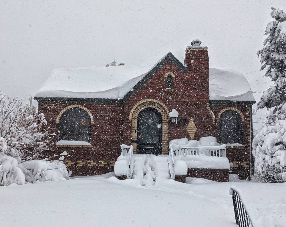 Red brick house in the snow with SW Pewter Green paint color.