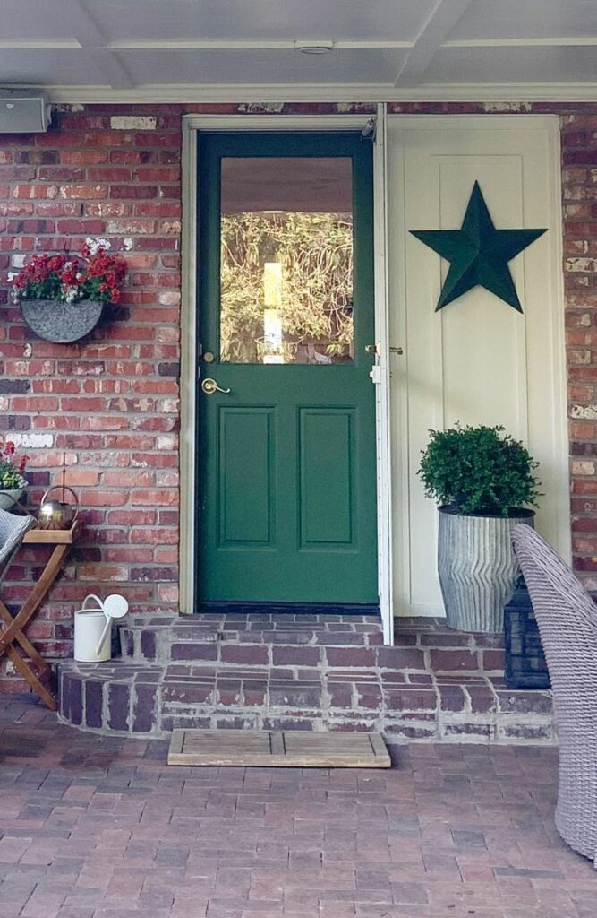 Red brick covered porch with green back door