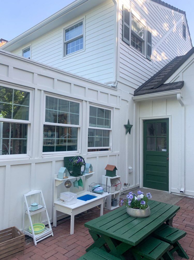 Red brick patio with SW Greek Villa siding and a green back door