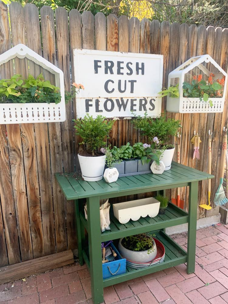 Red brick patio with flowers and green plant stand
