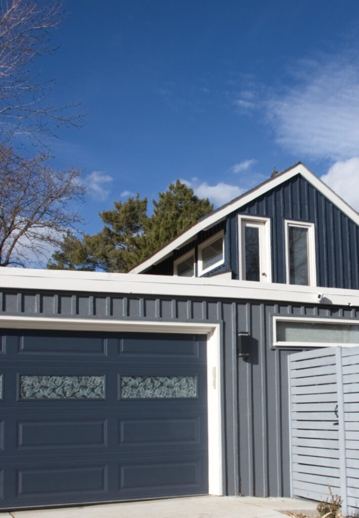 Mid-Century modern house with BM Hale Navy garage door and siding with BM Stormy Sky accents and BM Pale Oak trim.